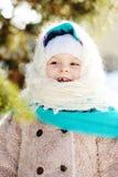 一件蓬松围巾和外套的小女孩在背景中笑 免版税图库摄影