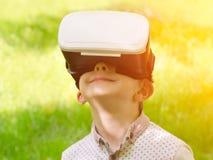 一件虚拟现实盔甲的男孩在绿草背景  库存照片