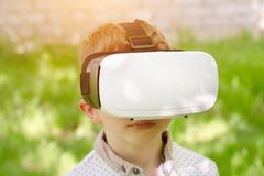 一件虚拟现实盔甲的男孩在绿草背景  免版税库存照片