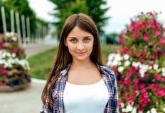 一件衬衣的女生男小学生在公园立场的夏天在花背景  愉快微笑,休息 库存图片