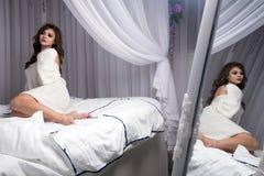 一件被编织的毛线衣的一个可爱的白肤金发的女孩在弯曲她的腿的一张白色床上 反射是可看见的在镜子 免版税库存照片
