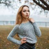一件被编织的毛线衣的俏丽的妇女在一有雾的秋天天 免版税图库摄影