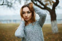 一件被编织的毛线衣的年轻美丽的女孩在一有雾的秋天天 图库摄影