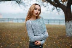 一件被编织的毛线衣的时髦的女孩在一有雾的秋天天 图库摄影