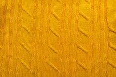 一件被编织的毛织物品的纹理 创造一个冬天布局的背景,圣诞卡,横幅 编织黄色毛线衣 免版税库存照片