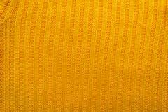 一件被编织的毛织物品的纹理 创造一个冬天布局的背景,圣诞卡,横幅 编织黄色毛线衣 图库摄影