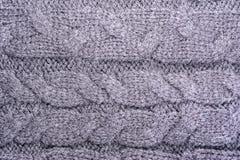 一件被编织的毛织物品的表面的纹理与猪尾样式的,抽象背景 图库摄影