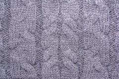 一件被编织的毛织物品的表面的纹理与猪尾样式的,抽象背景 库存照片