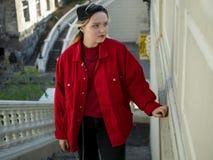 一件被编织的黑帽会议和红色夹克的可爱的白肤金发的行家女孩在台阶站立在桥梁下 免版税图库摄影