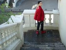 一件被编织的黑帽会议和红色夹克的可爱的白肤金发的行家女孩在台阶站立在桥梁下 图库摄影