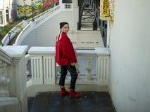 一件被编织的黑帽会议和红色夹克的可爱的白肤金发的行家女孩在台阶站立在桥梁下 免版税库存图片