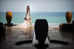 一件豪华白色礼服的新娘在海洋的背景站立在水罐中间 库存照片