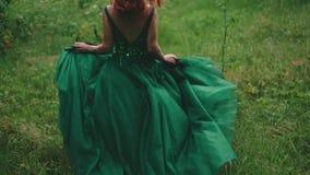 一件豪华绿色礼服的红发女孩有闪耀的成串珠状 公主通过森林沼地,一列长的火车跑 股票视频
