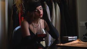 一件豪华黑减速火箭的礼服的一名妇女坐在与书和饮用的科涅克白兰地的一张桌上 影视素材
