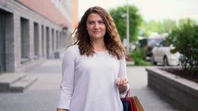 一件轻的礼服的一个女孩有长的头发的在购物以后运载与购买的包裹在她的手上 慢的行动 股票录像