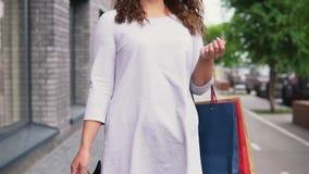 一件轻的礼服的一个女孩有长的头发的沿着走街道在购物以后有一种好心情并且运载包裹与 影视素材