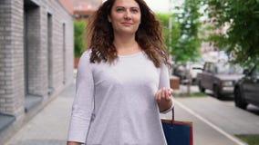 一件轻的礼服的一个女孩有长的头发的沿着走街道在购物以后有一种好心情并且运载包裹与 股票视频