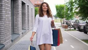 一件轻的礼服的一个女孩步行沿着向下街道在购物以后 慢的行动 影视素材