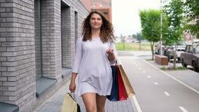 一件轻的礼服的一个女孩沿着走街道在购物以后并且运载与购买的包裹在她的手上 慢 股票录像