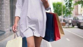 一件轻的礼服的一个女孩沿着走街道在购物以后有一种好心情并且运载与购买的包裹 股票视频