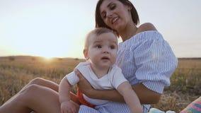 一件轻的礼服的一个少妇坐在领域的与一个可爱的婴孩的草和戏剧 迷住的画象 股票视频