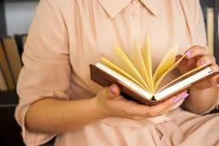一件轻的礼服的女孩读一本书 女性手在他们的手上拿着一本书 库存图片