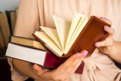 一件轻的礼服的女孩读一本书 女性手在他们的手上拿着一本书 库存照片