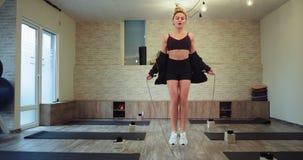 一件运动服的吸引人白肤金发的夫人使用对得到更多肌肉的跳的一条绳索非常在一大有氧集中了 股票录像