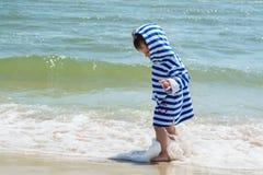 一件镶边长袍的一个小孩子在海滨在水中站立并且看他的湿腿认识世界, 免版税库存图片