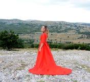 一件长的猩红色礼服的一个女孩在山的一个森林里 库存图片