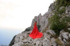 一件长的猩红色礼服的一个女孩在山的一个森林里 免版税库存照片
