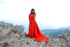 一件长的猩红色礼服的美丽的妇女在山的一个森林里 免版税库存图片
