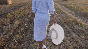 一件长的礼服的一个亭亭玉立的女孩在与一个大帽子的蓝色小条在她的手上在金黄领域走在夏天在 影视素材