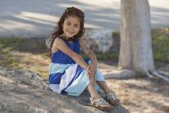 一件长的礼服的一少女坐一个大岩石在一棵树下在佛罗里达公园 库存图片