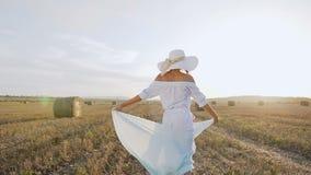 一件长的礼服的可爱的女孩,有围巾的大帽子在日落夏天转动她自己领域的 秀丽年轻人 影视素材