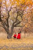 一件长的礼服的美丽的母亲在一件红色外套的小女儿在老附近秋天庭院生节的取决于的摇摆摇摆 库存图片