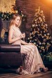 一件长的金黄礼服的典雅的年轻白肤金发的妇女坐椅子和饮用的香槟,拿着在的一个酒杯 免版税库存图片