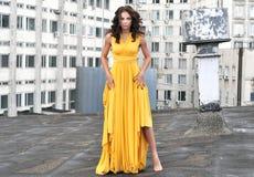 一件长的黄色礼服的女孩在一个大厦的屋顶在城市 免版税库存照片