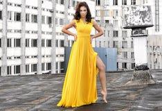 一件长的黄色礼服的女孩在一个大厦的屋顶在城市 库存照片