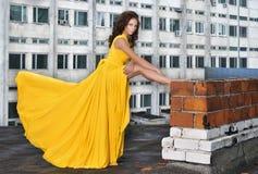 一件长的黄色礼服的女孩在一个大厦的屋顶在城市 免版税库存图片