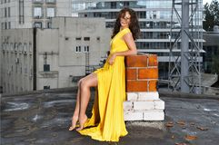 一件长的黄色礼服的女孩在一个大厦的屋顶在城市 图库摄影