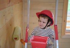一件防护盔甲的一个逗人喜爱的小男孩绘一个木房子的墙壁有路辗的,站立在活梯 免版税库存图片