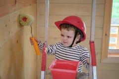 一件防护盔甲的一个逗人喜爱的小男孩绘一个木房子的墙壁有路辗的,站立在活梯 免版税图库摄影