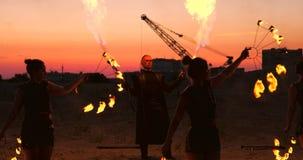 一件雨衣的一个人有两台火焰喷射器的放掉一个火热的火焰身分在沙子的日落 股票视频