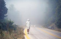 一件雨衣的年轻女性在雾的路 雨衣的搭车在雨中的妇女旅行  免版税库存图片