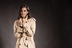 一件雨衣的深色的女孩在灰色背景 免版税库存图片