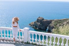一件雪白礼服和一个帽子的一个女孩有一个宽边缘的敬佩海和岩石的看法 库存图片