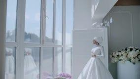 一件雪白礼服的一美丽的美女站立在一个大轻的窗口 她惊人美丽 一个卓越的图 影视素材