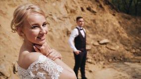 一件雪白礼服的一美女看照相机和微笑 女孩在沙子土墩背景站立  股票录像