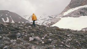 一件黄色外套的一个人走在积雪的领域的 股票视频